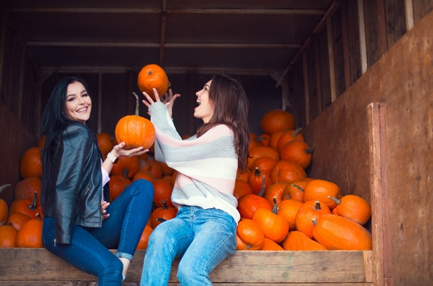 Two women laughing candidly surrounded by pumpkins is the perfect picture pose to pair with pumpkin quotes for Instagram.