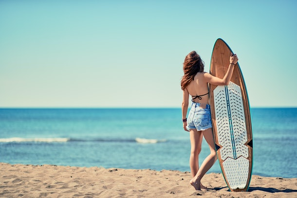 Young surfer girl at the beach with her surfboard looking for the waves