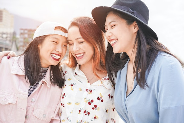 Asian women friends having fun outdoor in a sunny day - Happy trendy girls laughing together - Millennial generation, bonding, friendship and gathering concept - Focus on two left faces