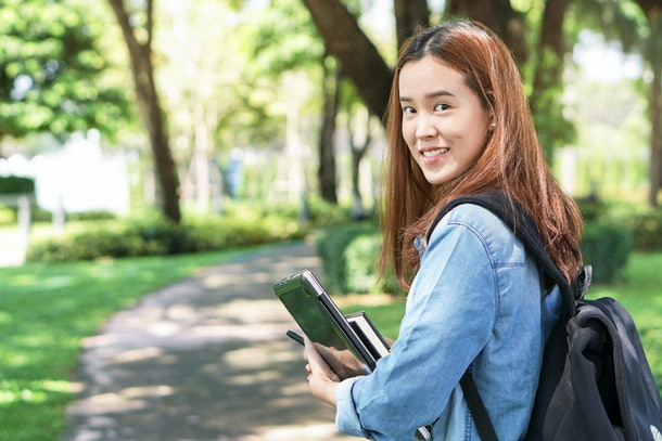 Portrait of asian female colleges student holding textbook in her hands and standing outdoors at university campus