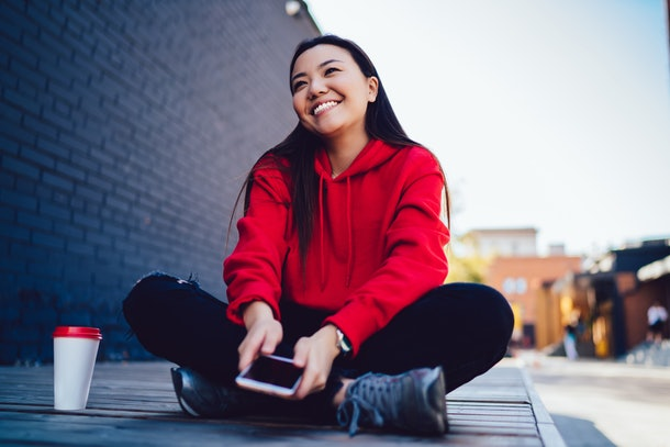 Takeaway cup with copy space area for advertising text, happy Asian female blogger with modern cellular gadget in hands feeling excited spending recreation time outdoors in sunny day. Carefree woman