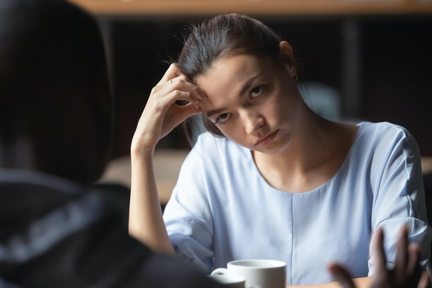 Bored unhappy girlfriend listening to African American boyfriend in cafe, bad first impression and date concept, multiracial couple having sitting at table, talking, having problem in relationships