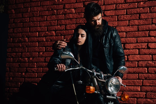 hipster couple. hipster couple riding on motorbike. hipster couple on brick wall background. road trip of hipster couple. planning week