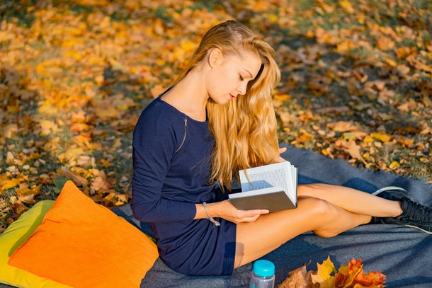 young female in the autumn park. A woman in an autumn park is reading a book, lying on a plaid, autumn reading pleasure.