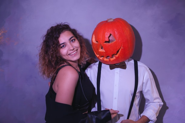 Unusual couple at the Halloween party. Man with carved pumpkin on his head and funny woman near pumpkin boy