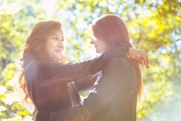 Happy, red-haired best friends hugging in the park during autumn weather