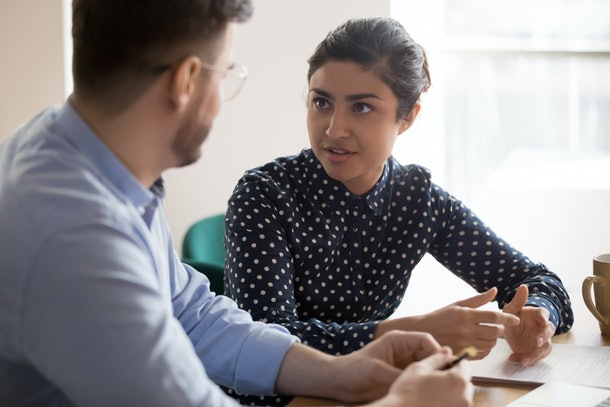 Young indian female mentor coach worker talking to male coworker teaching intern having business conversation with workmate, serious hindu manager helping colleague discussing new project in office