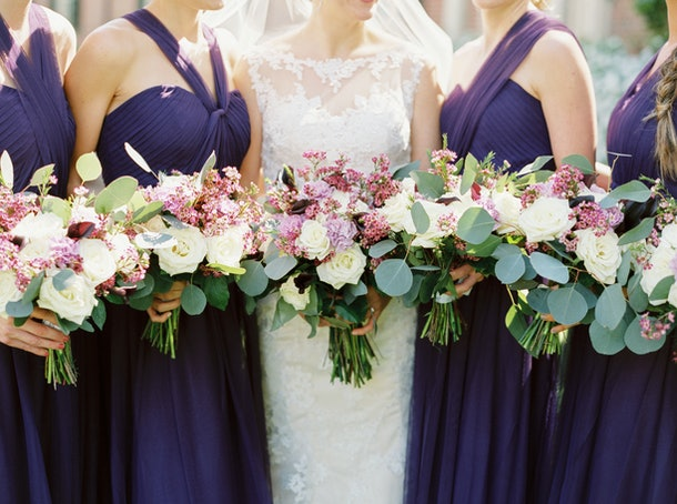 Bride with Bridesmaids in Purple Dresses Holding White and Purple Bouquets