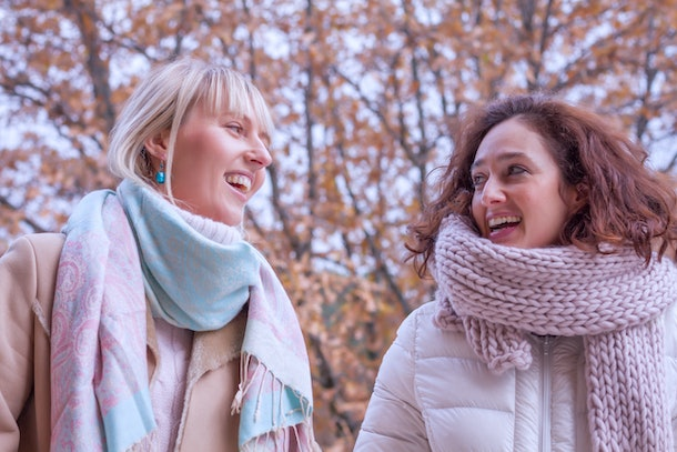 Happy female couple laughing while they look.