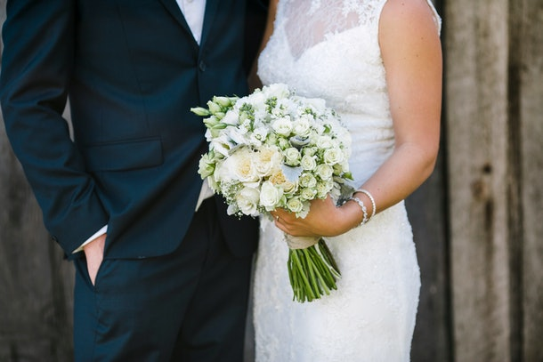 Close up of bride and groom with bride holding classic white and green floral bouquet