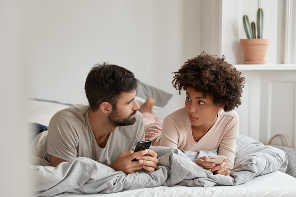Lovely mixed race couple have pleasant talk, use mobile phones in bed at morning, look seriously at each other, enjoy coziness at bedroom, free wifi connection at home. Contemporary technology