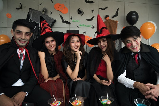 Group of young people in spooky Halloween costume with sweet candy and nectar on the table, October event