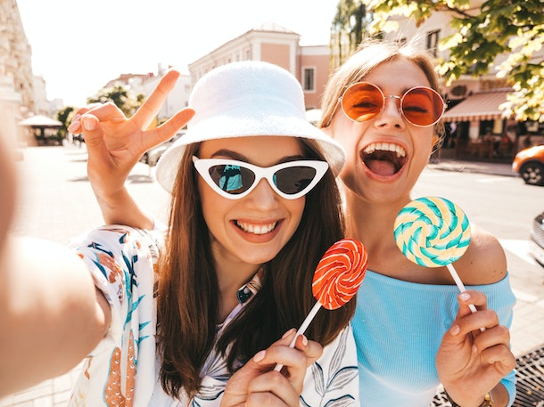 Two young smiling hipster women in casual summer clothes. Girls taking selfie self portrait photos on smartphone.Models posing on street background in sunglasses and panama hat.Eating candy lollipop