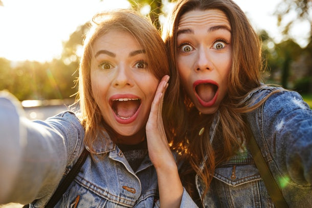 Portrait of two shocked screaming girls making funny faces while taking a selfie outdoors