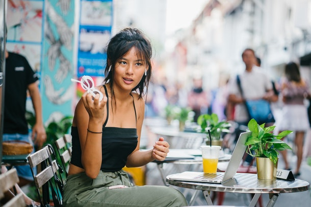 A portrait of a trendy, young and attractive Chinese Asian Singapore millennial teenager girl sitting and chilling at a cafe along the crowded Haji Lane in Bugis, Singapore, during the day.