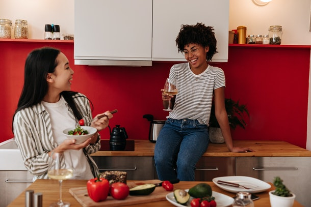 Women in stylish clothes having fun and communicating in kitchen at dinner with champagne