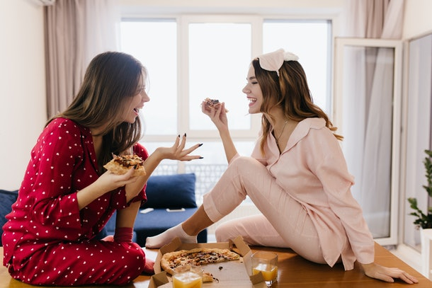 Inetersted girls talking around and eating cheese pizza. Indoor photo of lovable dark-haired ladies enjoying weekend at home with fast food.