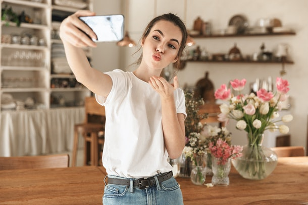 Image of attractive smiling woman wearing casual clothes taking selfie photo on cellphone and blowing air kiss in cozy kitchen