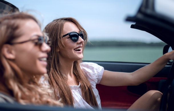 two girlfriends in a convertible car