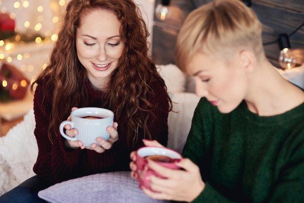 Beautiful girls drinking hot tea with lemon in winter day