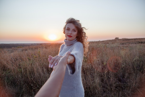 Close-up of the man hand holding the hand with married ring of his pregnant woman against the field and sunset. woman wearing the knitted dress