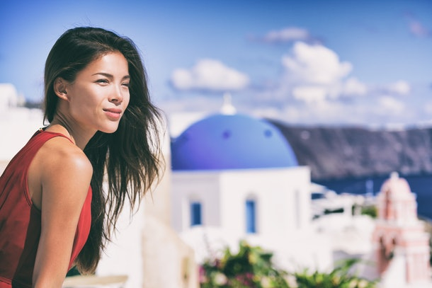 Luxury Europe cruise travel vacation Santorini woman looking at view. Tourist Asian girl relaxing at three blue domes, Oia, Greece, european destination.