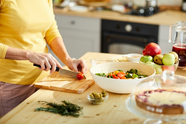 Close-up of unrecognizable woman in yellow sweater standing at kitchen counter and cutting tomato while cooking Greek salad