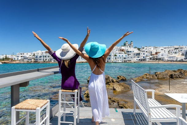 Two happy female traveller friends on a classic Greek summer setting of the cyclades in Greece with white houses and blue sea