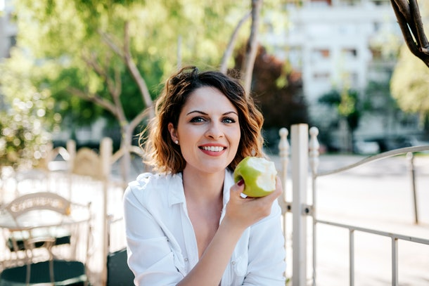 Portrait of beautiful woman eating apple in cafe outdoor.