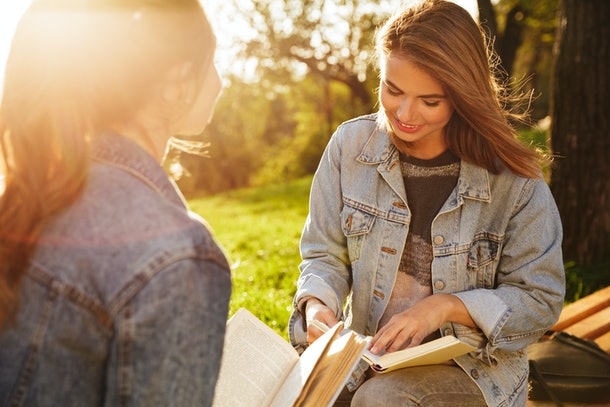 Close-up shot of two charming brunette female friends reading books in park at sunny day