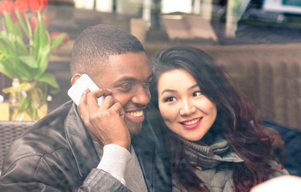 Interracial couple on date view through cafe window - Afro american man using phone and asian girlfriend facial expression in love - Cheerful mixed race friends - Closeup from glass focus on male
