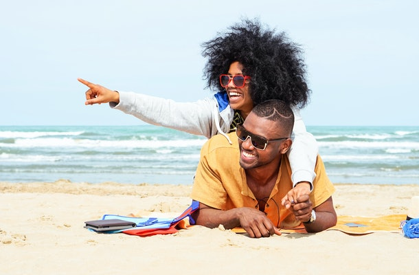 Young afro american couple  pointing finger relaxing on beach - Cheerful african friends having fun at day on blue ocean background - Concept of lovers happy moments on summer holiday - Vintage filter