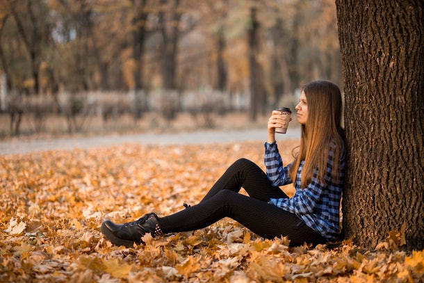 Fall concept. Happy and cheerful woman drinking coffee while sitting on park leaves under fall foliage. Beautiful young modern woman smiling