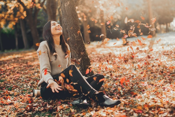 Happy Autumn. Beautiful woman having fun in fall park.