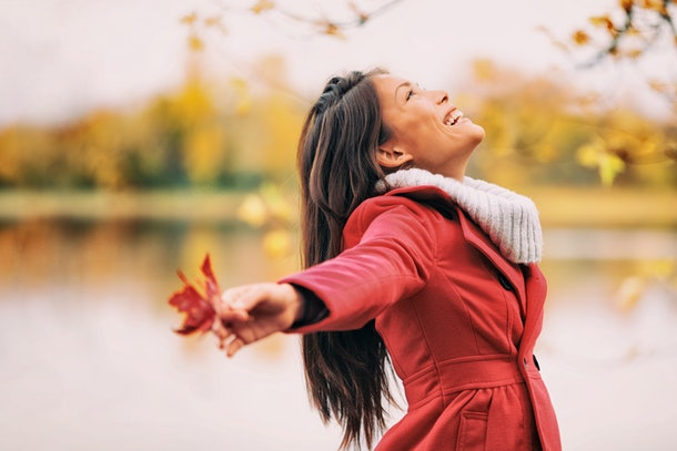 Autumn woman happy smiling feeling free in fall nature. Nature people beauty landscape. Girl by the lake.