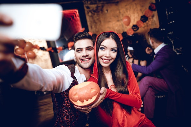 Halloween party. A guy in a vampire costume and a girl in a red dress with a hood making selfie with a pumpkin-lamp. Behind them sit their friends and relax