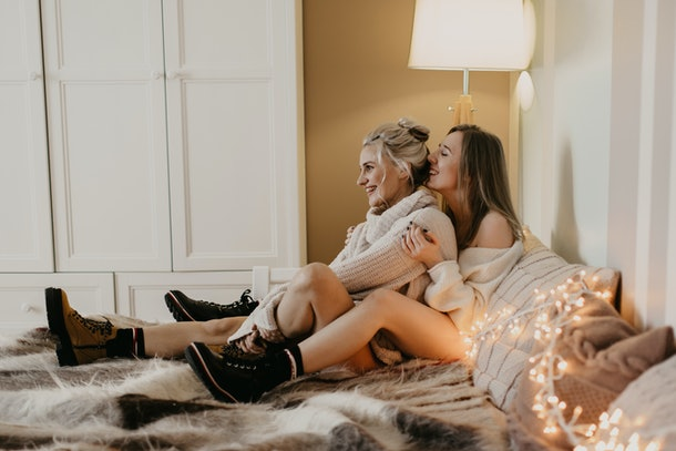 Beautiful girls in love cuddle in bed and laugh, the light from the garlands