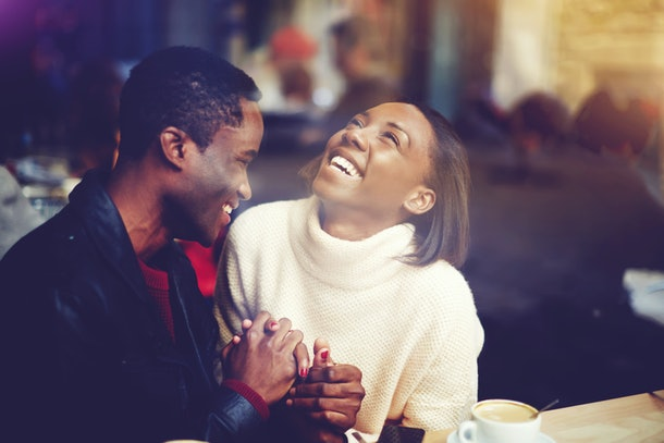 Young happy man and woman laughing together while sitting in modern restaurant during coffee break, cheerful couple in love with smiles on faces enjoying rest and good day while relaxing in bar