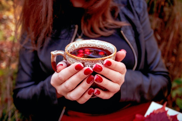 Autumn. Girl with bright red nails siting in autumn park and holding cup of tea with dogrose berries. Close up.