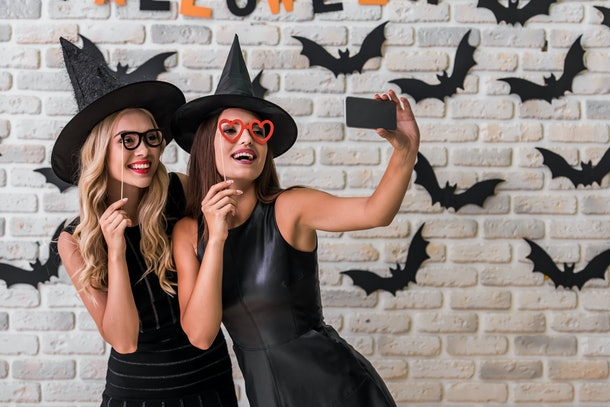 Beautiful girls in black dresses and witch hats are holding party props and doing selfie using a smart phone, on background decorated for Halloween