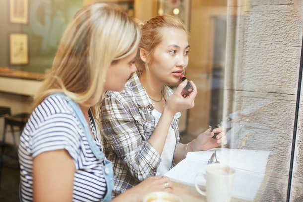 Portrait of two women in casual clothes sitting in a cafe. Female friends applying lipstick properly during their lunch in cosy place. Attractive girls sitting near the window with coffee indoors.
