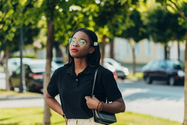 Young cool black skin girl with glasses walking in the street in the sammer day.
