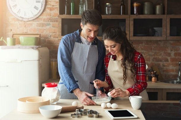 Happy young woman and man baking pie in loft kitchen. Young family cooking at home, using digital tablet. Mockup for recipe