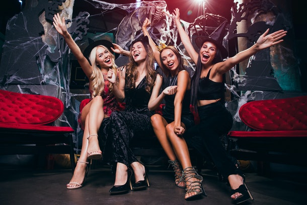 Come celebrate with us! Four beautiful young women in evening gown looking at camera with smile while celebrating Halloween in nightclub