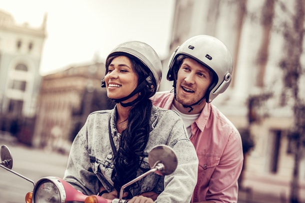 Having fun. Delighted happy couple having fun while riding a motorcycle together