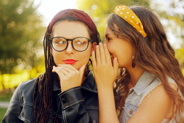 Two friends share secrets. Sisters gossip. Girl whispering a secret to her ear in ear. Two beautiful brunettes at sunset.