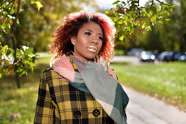 portrait of pretty dark-skinned beautiful girl with red curly magnificent hair. woman in plaid coat and scarf posing among trees in autumn