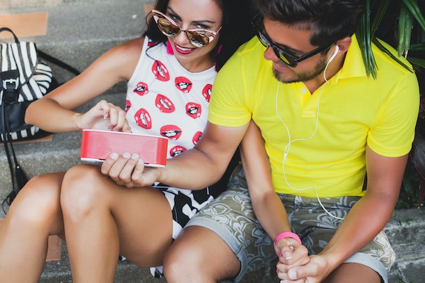 young hipster couple in love, listening to music on speaker, smiling happy, having fun, summer outfit, tropical vacation, sunglasses