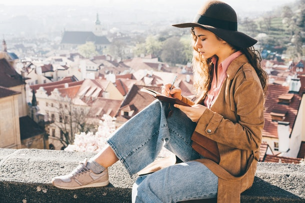 Woman in brown hat writing in the diary in view point with amazing view. Cute woman taking notes and wirting in notebook.