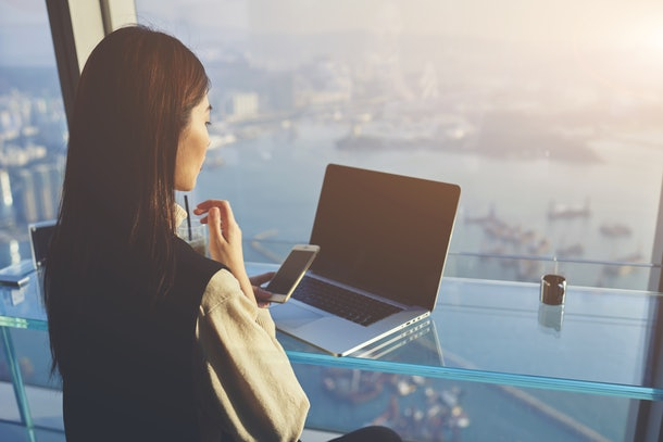 Woman owner of successful company is using mobile phone during video conversation in internet via net-book with staff during her business trip in New York, while is sitting in skyscraper building
